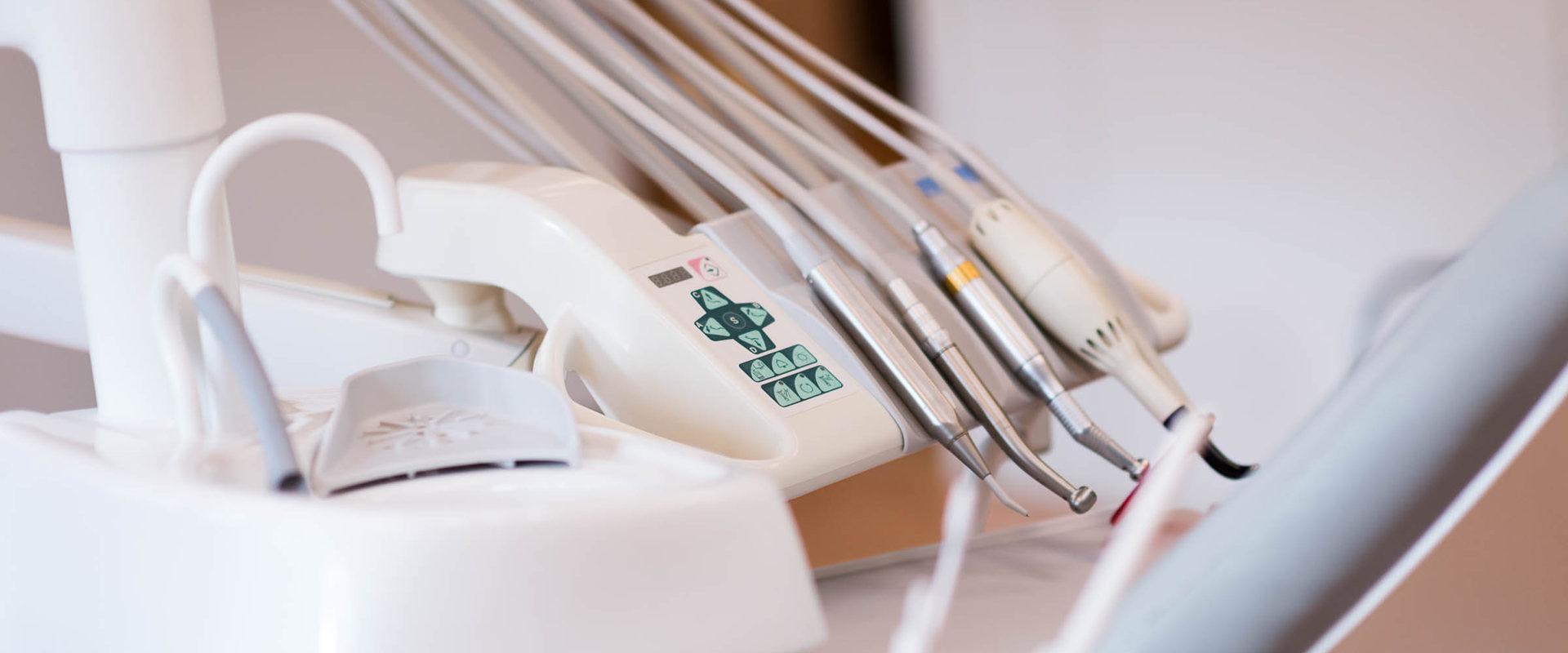 Nærbilde av tannlegeutstyr og skyllevask.