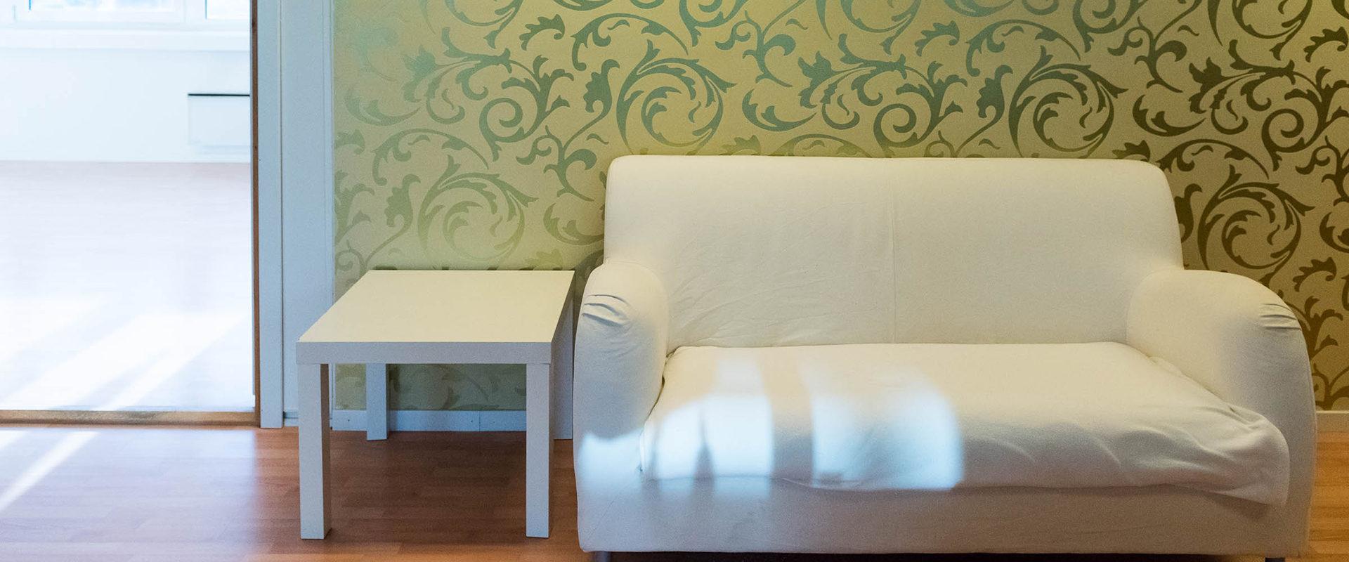 Bord og sofa ute i venteværelset.