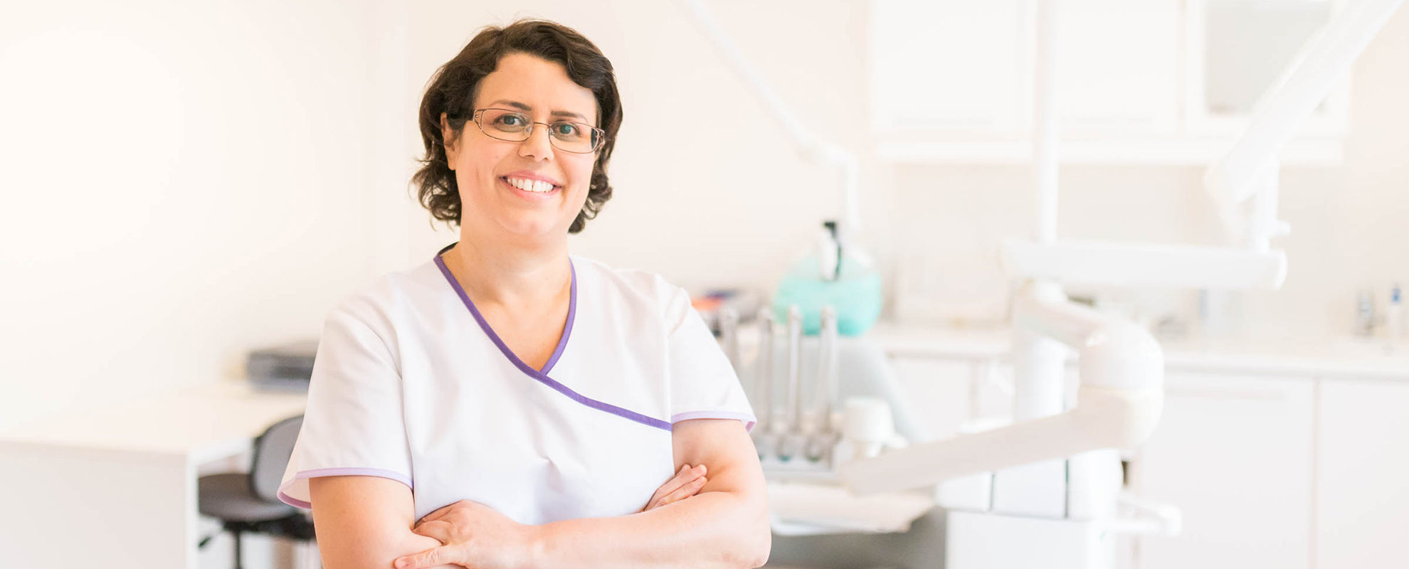 Tannlege Rana stående foran tannlegestol inne på kontoret.